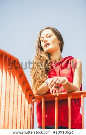 Young long haired girl leaning against railing on the urban bridge. Lifestyle funky in summer. Trendy sport teen. - stock photo