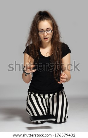 Young long-haired teenager in striped pants kneeling on the ground, dropped it out of the hand the tablet, which just falls down - stock photo