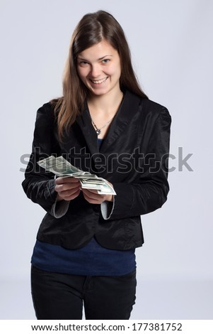 Young long-haired woman holding fan-shaped dollars in his hand - stock photo