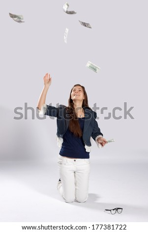 Young long-haired woman kneeling on the floor and throws dollars up to - stock photo