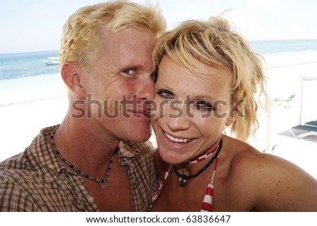 Young Love Blond Couple at the beach playing and kissing - stock photo