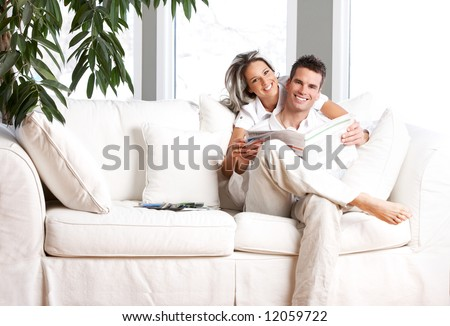 Young love couple reading magazine  in the comfortable apartment - stock photo