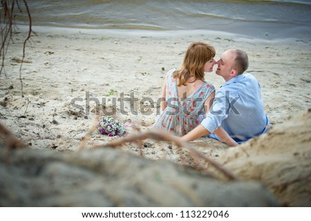 Young love Couple sit on bank of river - stock photo