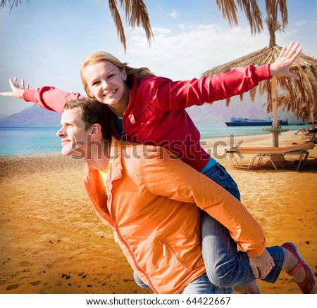 Young love Couple smiling under beach - stock photo
