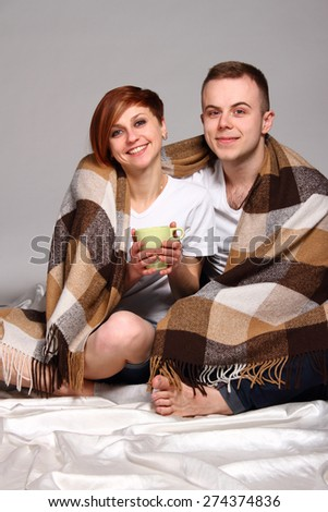 Young love couple under the covers with cup - stock photo
