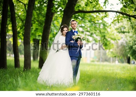 Young lovely and cheerfull wedding couple walking at the park