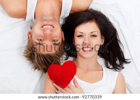 young lovely couple holding red heart together lying in a bed, happy smile looking at camera, valentine day love concept - stock photo
