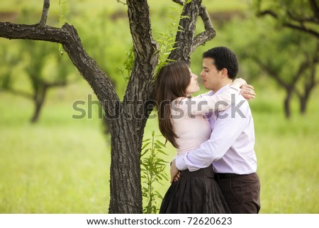 Young lovely couple looking each other in nature. - stock photo