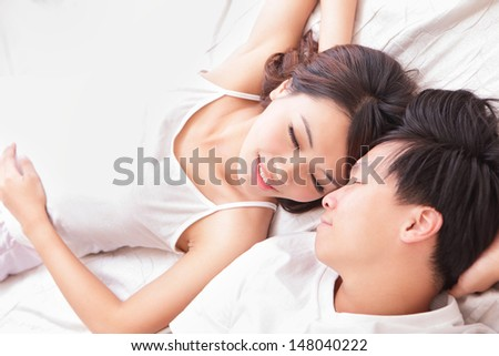 young lovely couple lying in a bed, happy smile looking to each other, top view, asian people - stock photo
