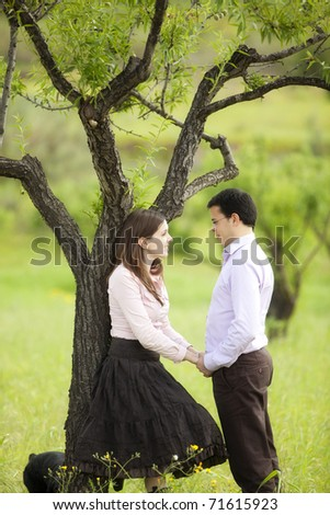 Young lovely couple staring each other in nature. - stock photo