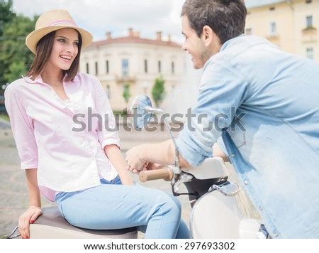 Young lovely couple talking to each other while woman sitting on scooter. Romantic date. - stock photo