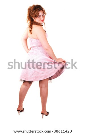 Young lovely girl in a pink dress and red long hair standing with her back to the camera, looking over her shoulder, on white background.