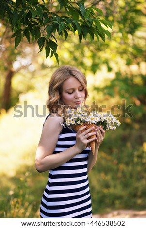 young lovely girl with chamomiles and waffle cones in hands