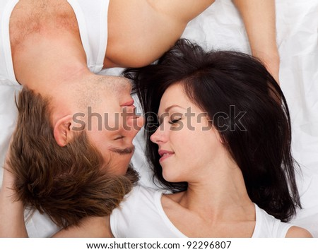 young lovely happy couple lying in a bed, sleep with closed eyes, top view. - stock photo