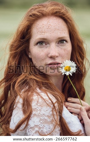 Young lovely smiling woman wonders on flower, tearing petals, close-up. - stock photo