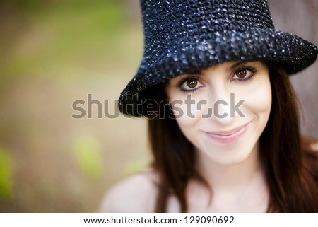 Young lovely woman portrait wearing hat under natural light. - stock photo