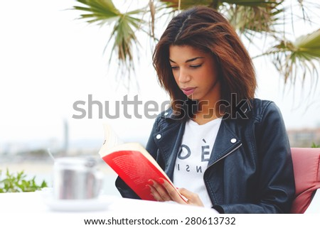 Young lovely woman sitting at coffee shop terrace pensive reading interesting book, afro american female enjoying a good book or novel during her recreation time outdoors at weekend - stock photo