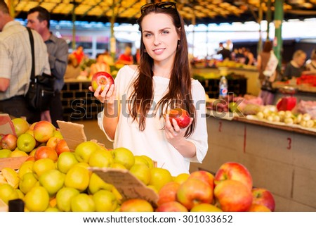Young lovely woman, wearing in white t-shirt, is selecting apples, during the shopping at fruit vegetable market, waist up - stock photo