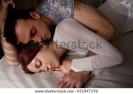 Young lovers couple laying together hugging in bed in home interior with moody light, hugs and affection, indoors home. Relationships lifestyle, bedroom passion. Boyfriend and girlfriend closeness. - stock photo
