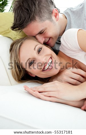 Young lovers having fun together on a sofa in the living-room - stock photo