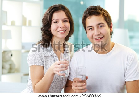 Young lovers holding glasses of water and looking at camera - stock photo