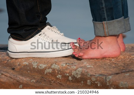 Young lovers in denim touch toes - stock photo