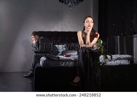 Young Lovers in Formal Wear Fighting for Something While Sitting at the Bedroom - stock photo