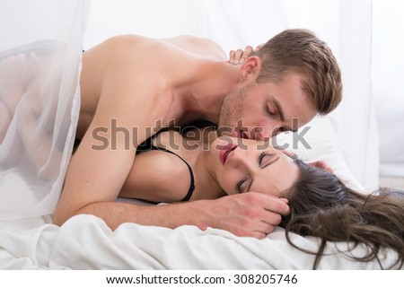 Young lovers lie in bed. - stock photo