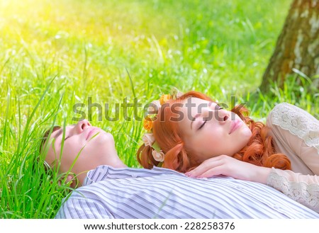 Young lovers resting outdoors, boyfriend and girlfriend lying down on fresh green grass with closed eyes, enjoying romantic relationship, love concept  - stock photo