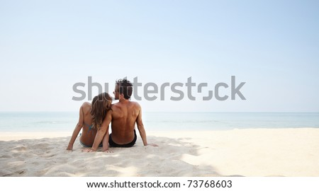 Young lovers sitting on warm sand at sunny day - stock photo
