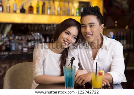 Young lovers spending an evening in a bar or a cafe over cocktails - stock photo
