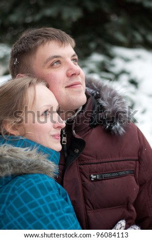 Young lovers woman and man in a winter forest