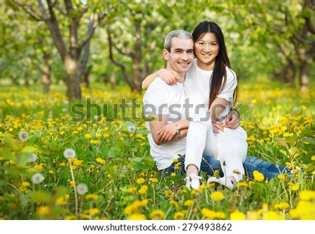 Young loving couple at the green grass with dandelion in the park park  - stock photo