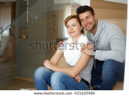 Young loving couple embracing in stairway, looking away, smiling. - stock photo