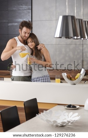 Young loving couple having orange juice in the morning at kitchen. - stock photo