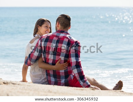 Young loving couple having romantic date on sandy beach at sunny day  - stock photo
