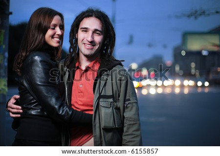 Young loving couple in a city. Girl tickling her boyfriend. - stock photo