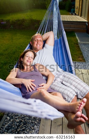 Young loving couple in a hammock in a summer setting. The woman is pregnant. - stock photo