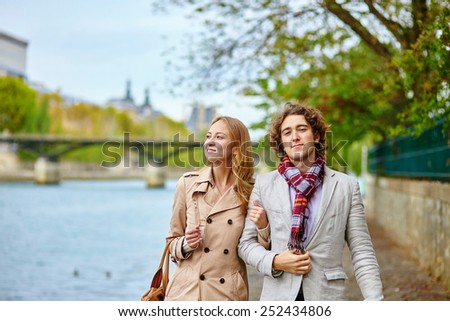 Young loving couple in Paris, on the Seine embankment