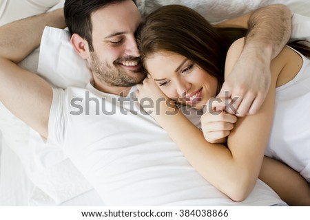Young loving couple in the bed - stock photo