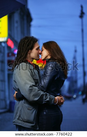 Young loving couple kissing in a city. - stock photo