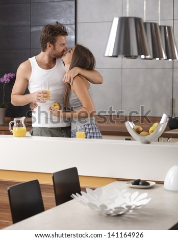 Young loving couple kissing in the kitchen in the morning, having breakfast. - stock photo