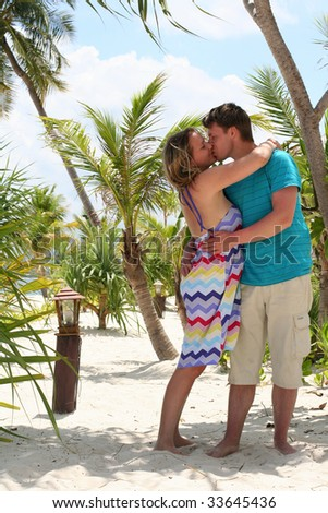Young loving couple kissing on sand beach of tropic paradise - stock photo