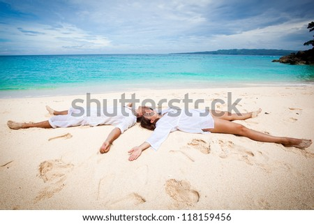 Young loving couple lying on beach, enjoying each other - stock photo