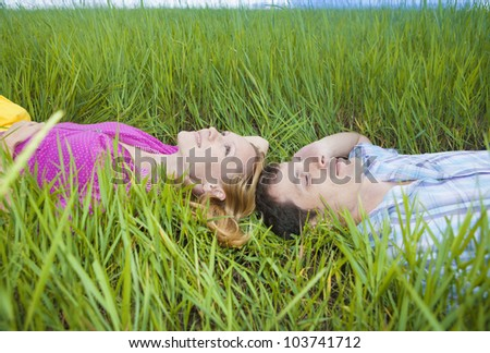 Young loving couple lying on green grass - stock photo