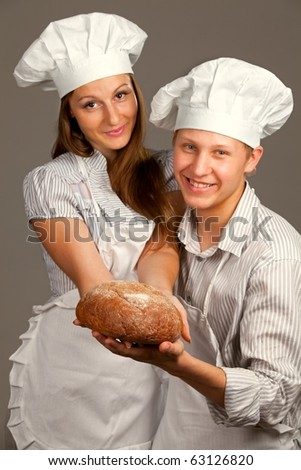 Young loving couple offer round loaf. Over gray background (focus on bread) - stock photo