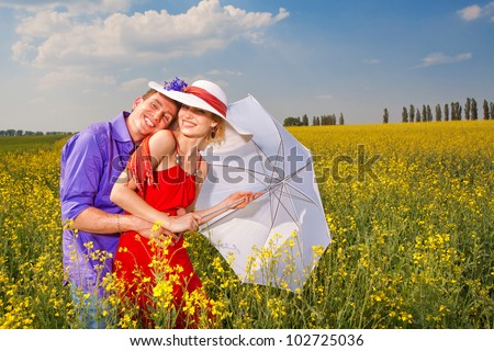 Young loving couple on a green field