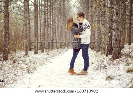 young loving couple on natural winter background. New Year and Christmas. - stock photo