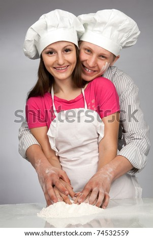 Young loving couple playing with dough. Over grey background - stock photo