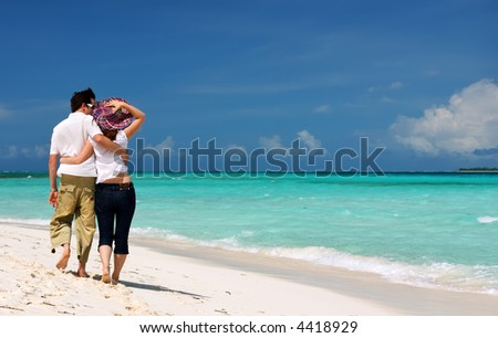 Young loving couple walking along tropical white sand beach - stock photo